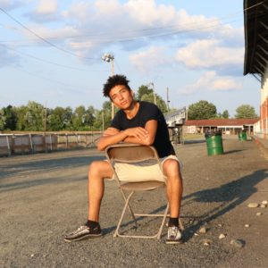 Aahnix poses for a picture on a chair, facing the sunset.