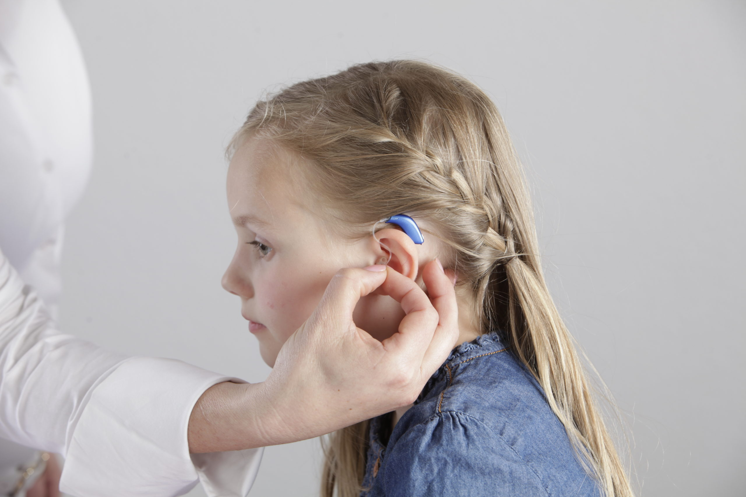 A young girl gets her hearing aid adjusted