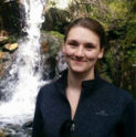 Charlotte smiles in front of a small waterfall
