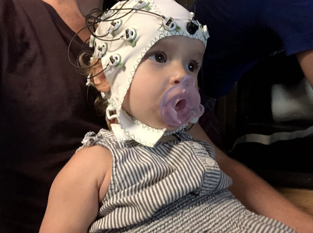 Clementine sits calmly in her father's lab, sucking a pacifier during an EEG experiment