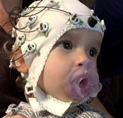 Clementine wears an eeg cap