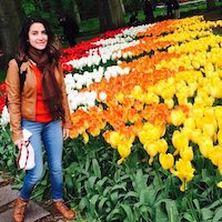Carla stands next to a bed of red, white, orange, and yellow tulips.