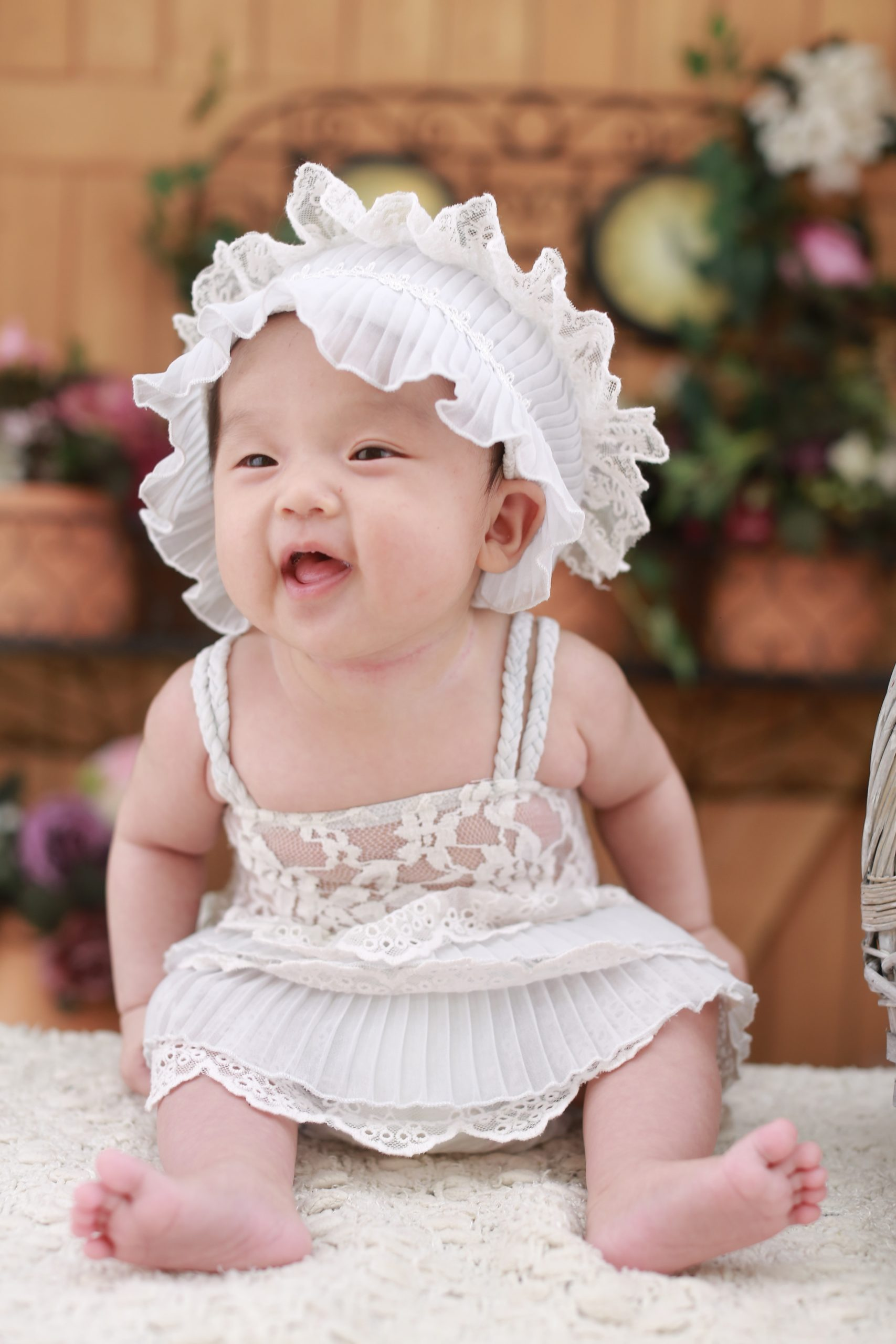 A sitting baby is dressed in a pinkish dress and a frilly lace bonnet.