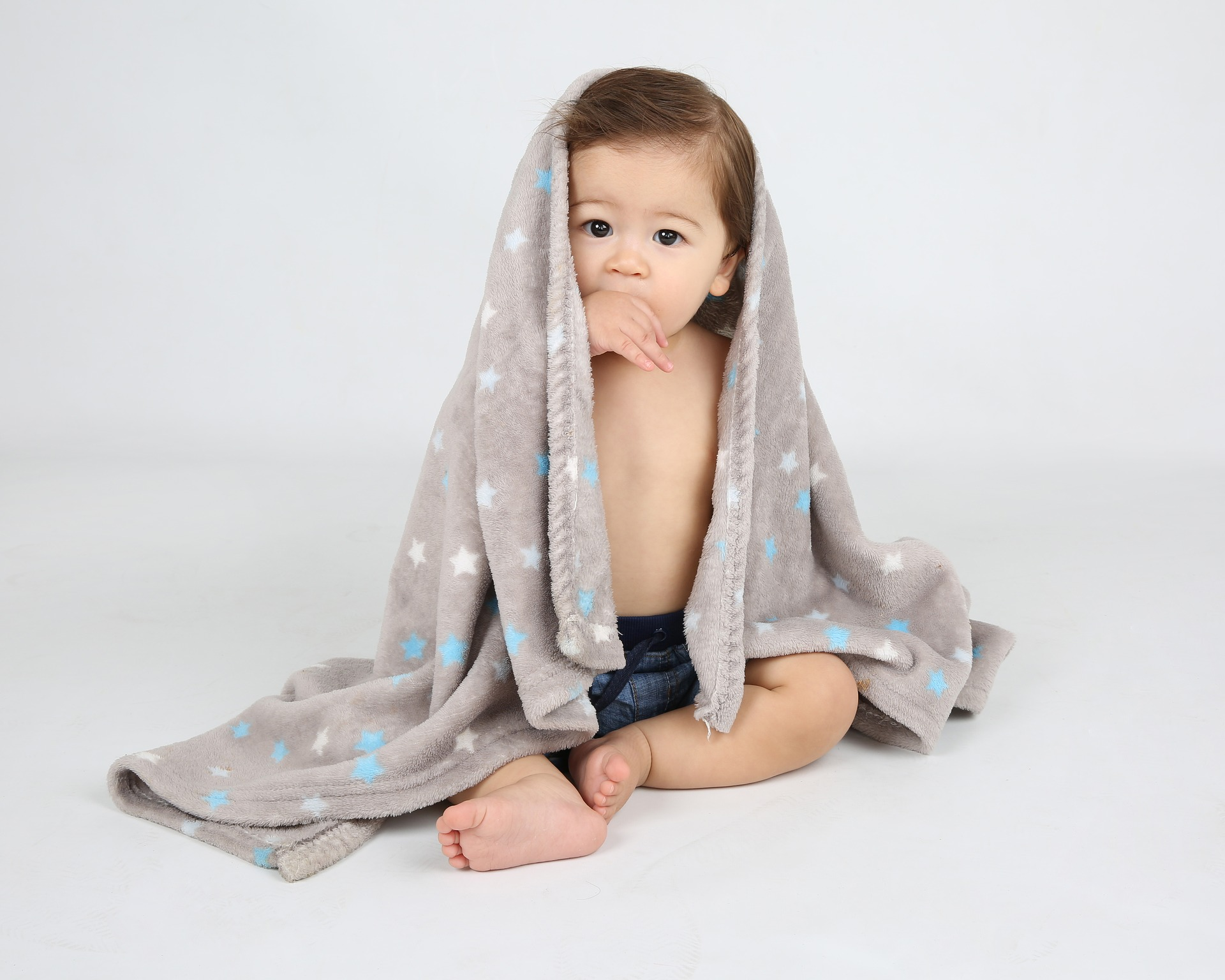 A baby sits against a white background while being draped in a grey blanket with different colored polka-dots.
