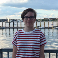 Hallie stands on a wooden pier