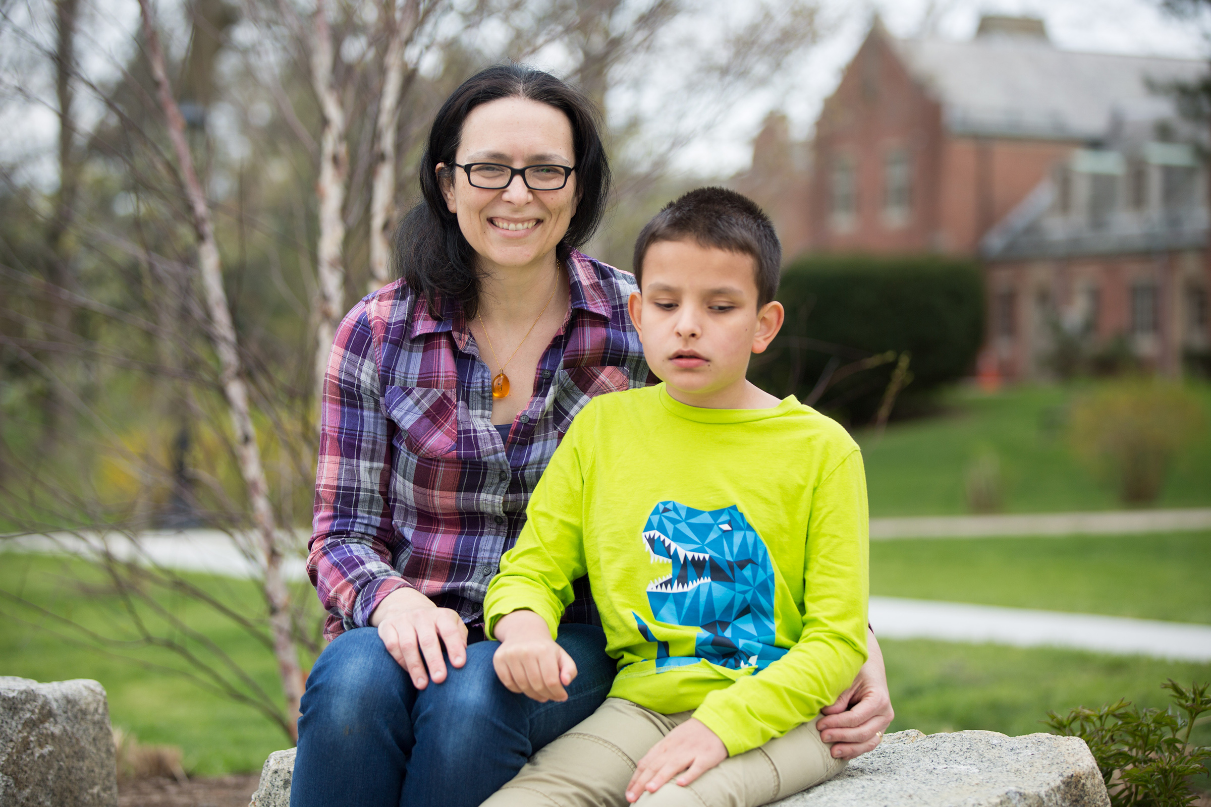 Amber and Ivan are seated on a large rock facing the camera. Amber is smiling, wearing a plaid shirt, jeans, glasses and an amber necklace. She has her arm around Ivan, who wears a green long-sleeve shirt with a blue t-rex and khakis. There are a few trees and buildings in the background.