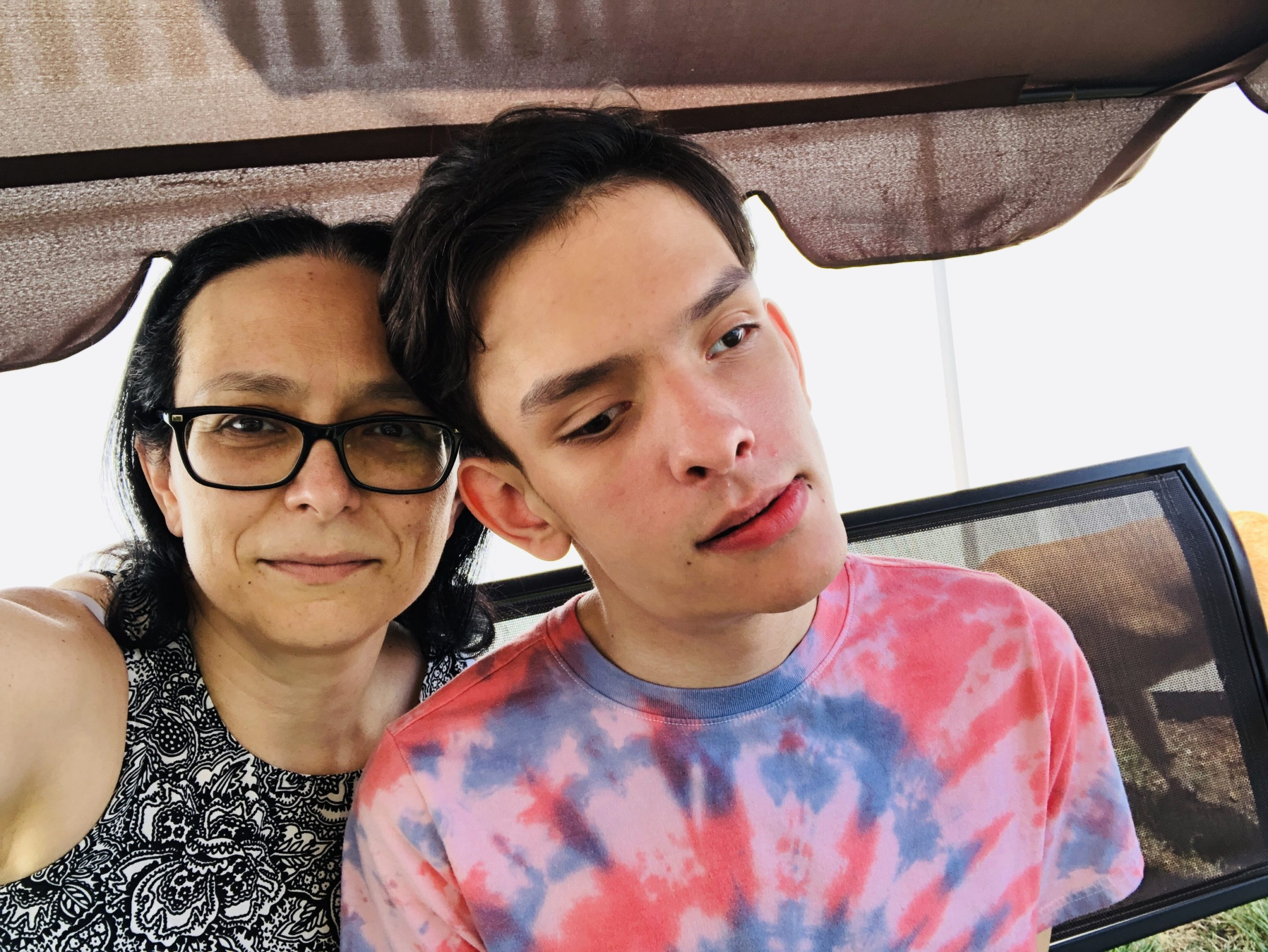 A selfie showing Amber on the left and Ivan on the right. Amber has long, dark brown hair, and wears a black and white patterend shirt and glasses. Ivan has short, dark brown hair and wears a red and blue tie-dye t-shirt.